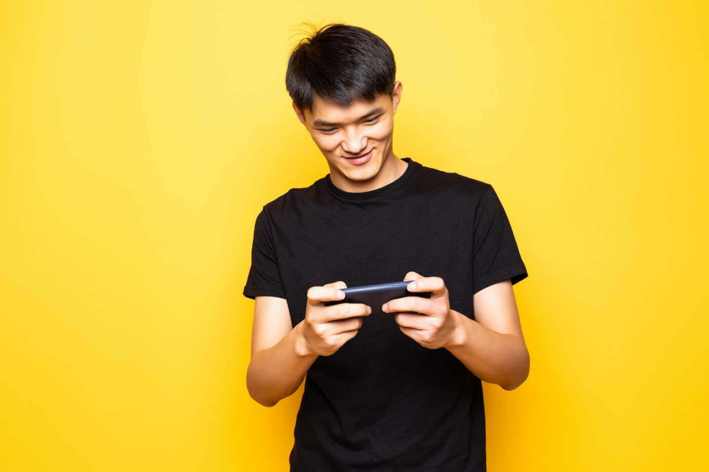 Young-asian-man-play-games-by-mobile-phone-standing-isolated-over-yellow-wall