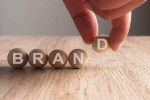 hand-putting-brand-word-written-wooden-ball