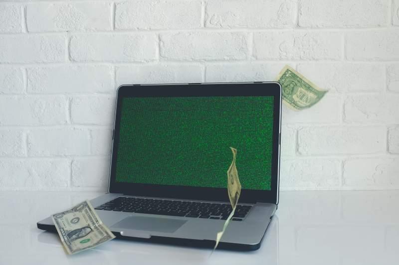 laptop and dollar bills